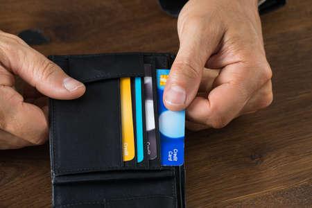 credit card: Imagen recortada de hombre de negocios que muestra la tarjeta de crédito en carpeta en el escritorio Foto de archivo