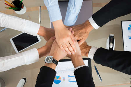 pledge: High Angle View Of Businesspeople Stacking Hands In Office Stock Photo