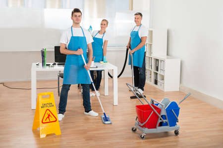 cleaning team: Cleaners Team In Uniform Cleaning Wooden Floor In Office