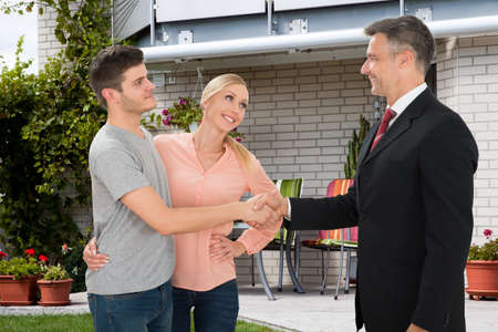 Mature Estate Agent Shaking Hands With Young Couple In Front Of House