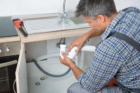 fontaneria: Vista lateral de fontanero madura la fijación de la tubería del fregadero en la cocina