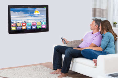 television remote: Couple Sitting On Sofa Watching Television In Living Room