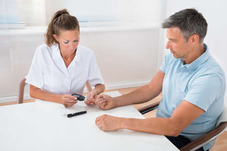 Female Doctor Checking Blood Sugar Level Of Patient In Hospital Banque d'images