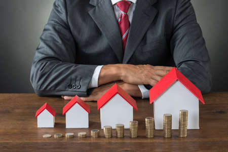 Midsection of businessman with different size houses and stacks of coins on table