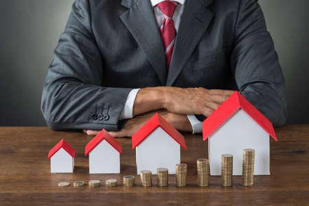 economia: Sección media de hombre de negocios con diferentes casas de tamaño y pilas de monedas en la mesa Foto de archivo