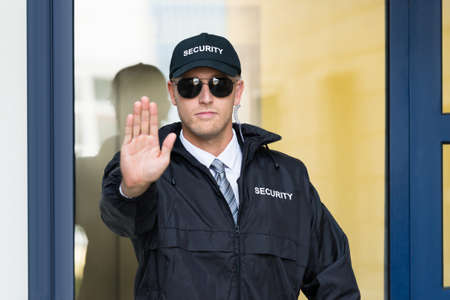 hand guard: Close-up Of A Male Security Guard Making Stop Sign With Hand Wearing Sunglasses