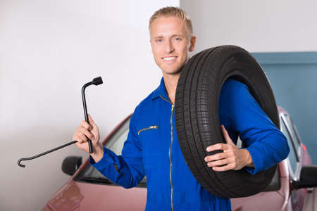 tire fitting: Portrait Of A Smiling Young Mechanic Holding Tire And Wrench Stock Photo