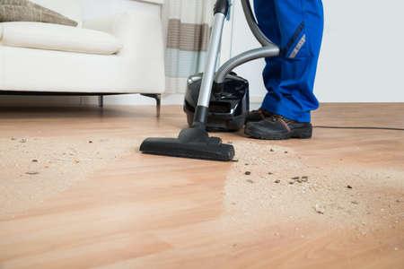 staub: Low Abschnitt der männlichen Pförtner Reinigung Boden mit Staubsauger im Wohnzimmer