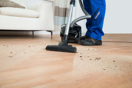 low: Low section of male janitor cleaning floor with vacuum cleaner in living room