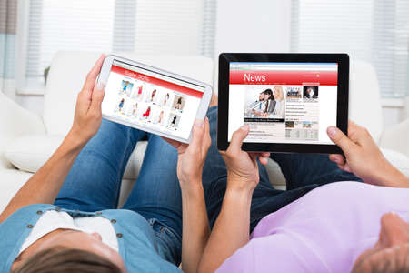 Mature Couple Online Shopping And Reading News On Digital Tablets At Home