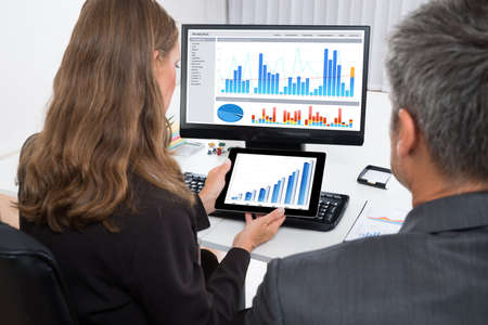 businesspeople: Two Businesspeople Analyzing Graph On Digital Tablet In Office