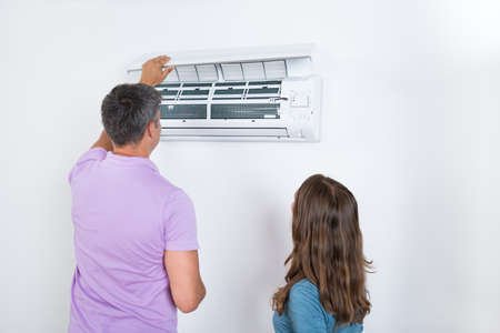 clean home: Couple Checking Air Conditioner Attached On White Wall