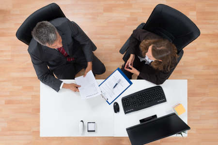 empleados trabajando: High Angle View Of Two Businesspeople Discussing On Documents In Office