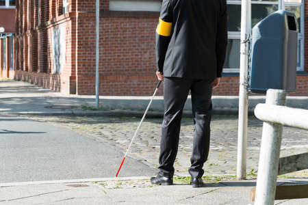blind person: Close-up Of A Blind Man Standing With White Stick On Street