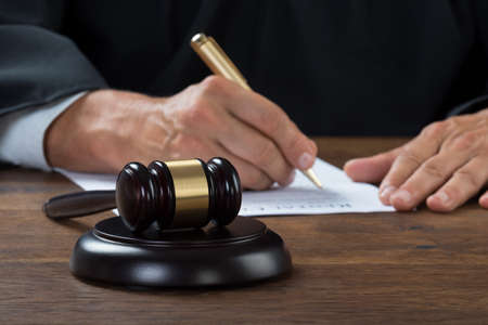 Midsection of judge writing on paper at table in courtroom Stock Photo