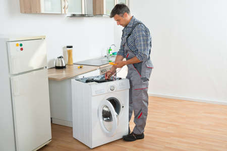 electrical appliance: Full length of technician checking washing machine with digital multimeter in kitchen