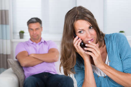secretly: Mature Woman Talking Secretly On Mobile Phone In Front Of Her Husband On Sofa