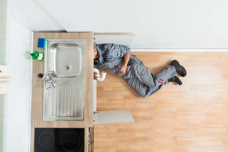 fontanero: Vista de �ngulo alto de fontanero que trabaja bajo fregadero de la cocina