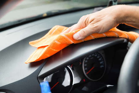 Cropped image of mature male worker cleaning car dashboard