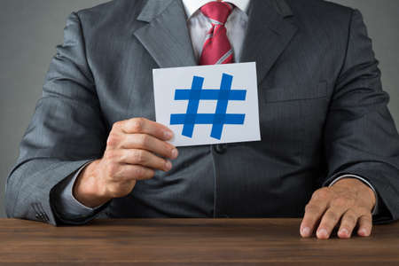 hash: Midsection of businessman showing hash sign on paper at desk Stock Photo