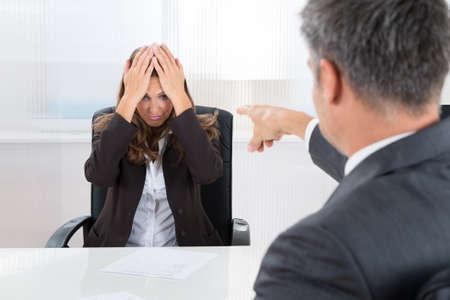 Hombre de negocios maduro que señala a la empresaria frustrada en la oficina