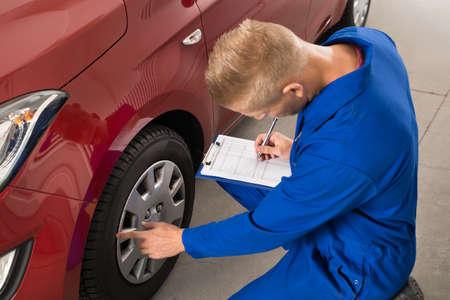 hombre escribiendo: Escribir Mecánico joven en el sujetapapeles blanco el examen de la rueda de coche Foto de archivo
