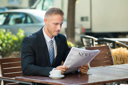 articles: Photo Of Businessman Sitting In Cafe Reading Newspaper
