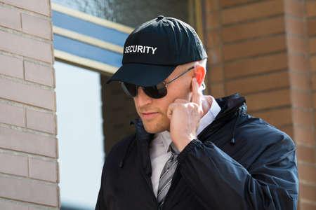 gorra policía: Primer De La Guardia de seguridad se coloca delante de la entrada escuchando el auricular Foto de archivo