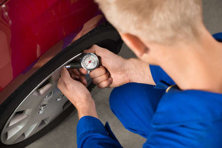 air pressure: Close-up Of Mechanic Checking Air Pressure Level In Car Tire