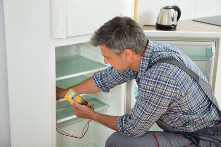 refrigerator kitchen: Mature male technician checking fridge with digital multimeter at home