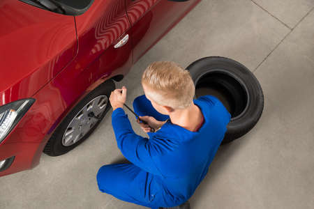 tire repair shop: High Angle View Of Mechanic Changing Tire In Garage With Wrench