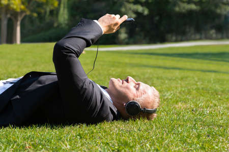listening device: Young Businessman Lying On Grass Enjoying Music On Headphone In Park Stock Photo