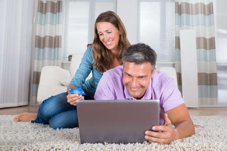 shop online: Portrait Of A Smiling Mature Couple Shopping On Laptop