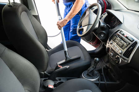 Midsection Of Man Vacuuming Car Seat With Vacuum Cleaner Stock Photo