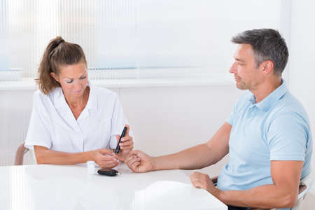 disease control: Female Doctor Using Lancelet On Mans Finger In Clinic Stock Photo