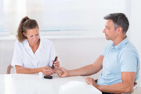 Female Doctor Using Lancelet On Mans Finger In Clinic Stock Photo