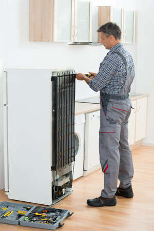 serviceman: Cropped image of serviceman working on fridge with screwdriver at home