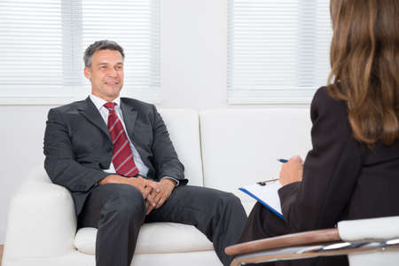 two men: Patient Sitting On Couch In Front Of Female Psychiatrist Writing On Clipboard Stock Photo