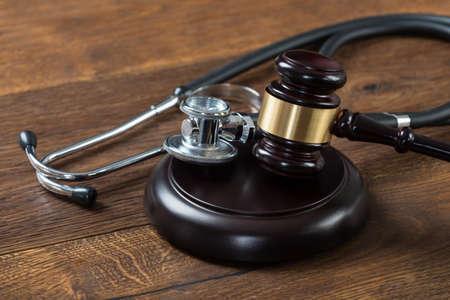 abogado: Primer plano de martillo y estetoscopio en el vector en sala