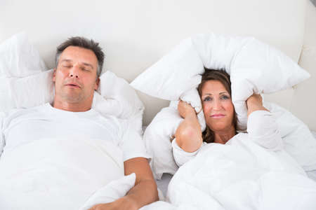 snoring: Woman Covering Her Ears With Pillow While Man Snoring