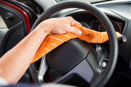 car detail: Cropped image of worker polishing car steering wheel Stock Photo