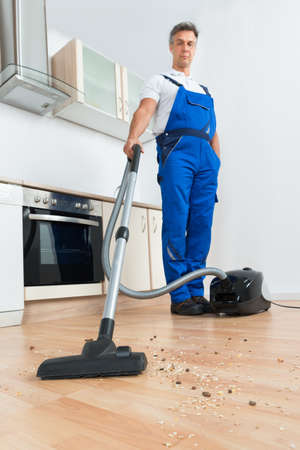 janitor: Full length of male janitor cleaning floor with vacuum cleaner in kitchen