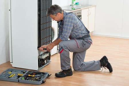 Full length of mature handyman repairing refrigerator at home