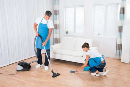 Two Cleaners In Uniform Cleaning Living Room