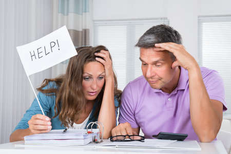 budget crisis: Worried Couple Sitting In Living Room Needs Help Due To Financial Crisis