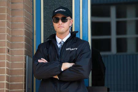 seguridad laboral: Guardia de seguridad confidente joven de pie brazos cruzados