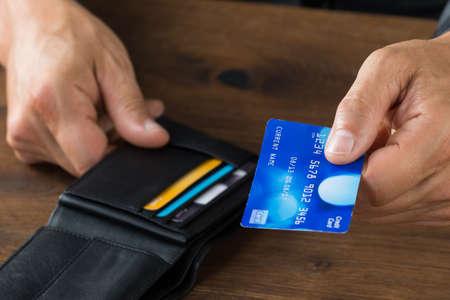 credit card: Recorta la imagen de hombre de negocios que da la tarjeta de crédito de la cartera en el escritorio