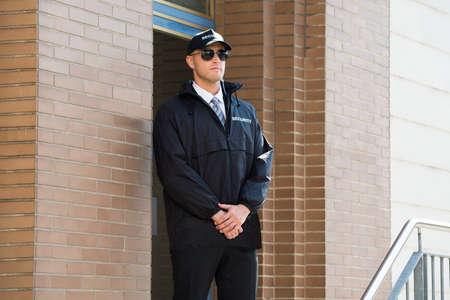 agent de s�curit�: Jeune Garde de s�curit� Homme debout � l'entr�e