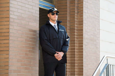 security: Young Male Security Guard Standing At The Entrance Stock Photo