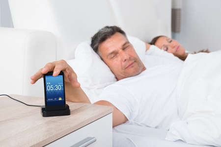 snoozing: Man On Bed Snoozing Alarm Clock On Cell Phone Screen While Sleeping Stock Photo